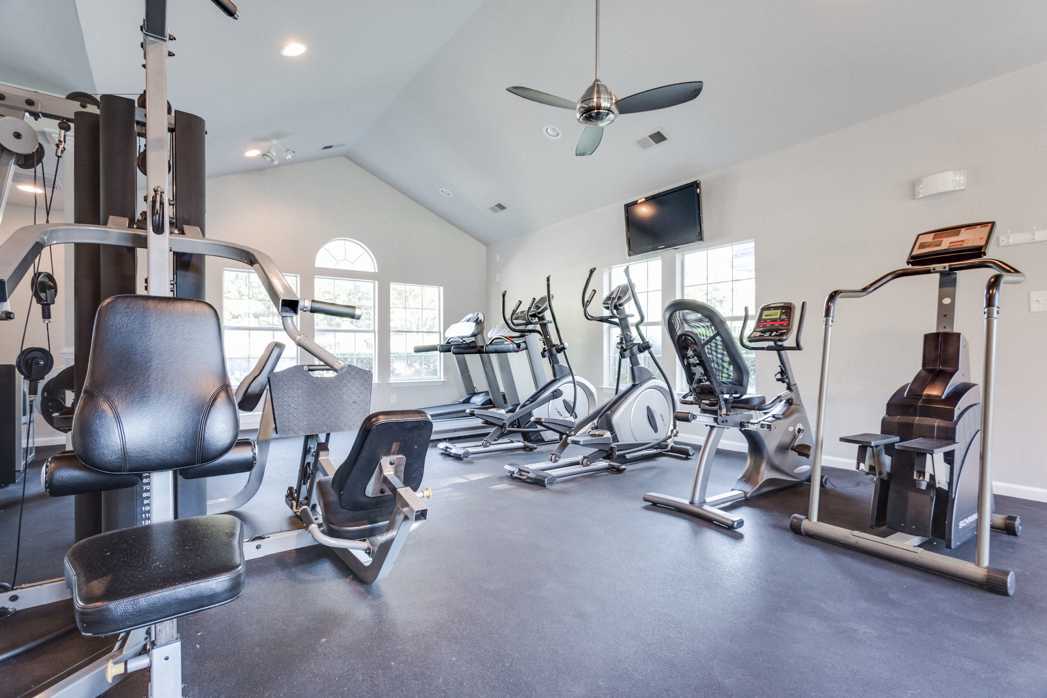 View of Fitness Center, Showing Weight Benches, Stair Stepper, Treadmills, Bike, Ceiling Fan, and Flat Screen TV at Midtown Crossing Apartments