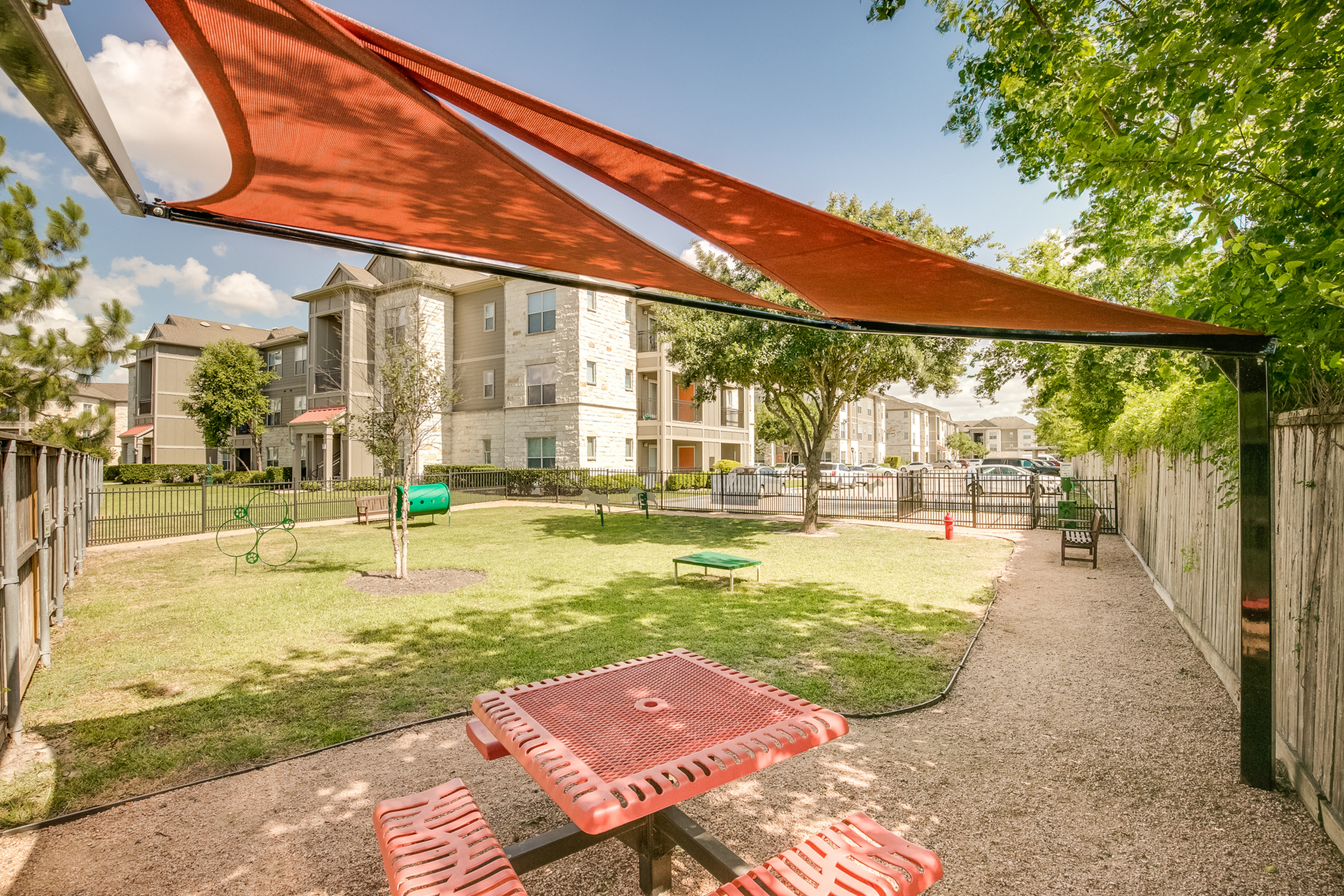 View of Fenced Pet Park, Showing Shaded Awning, Seating, and Doggy Agility Course  at Retreat at Stafford Apartments