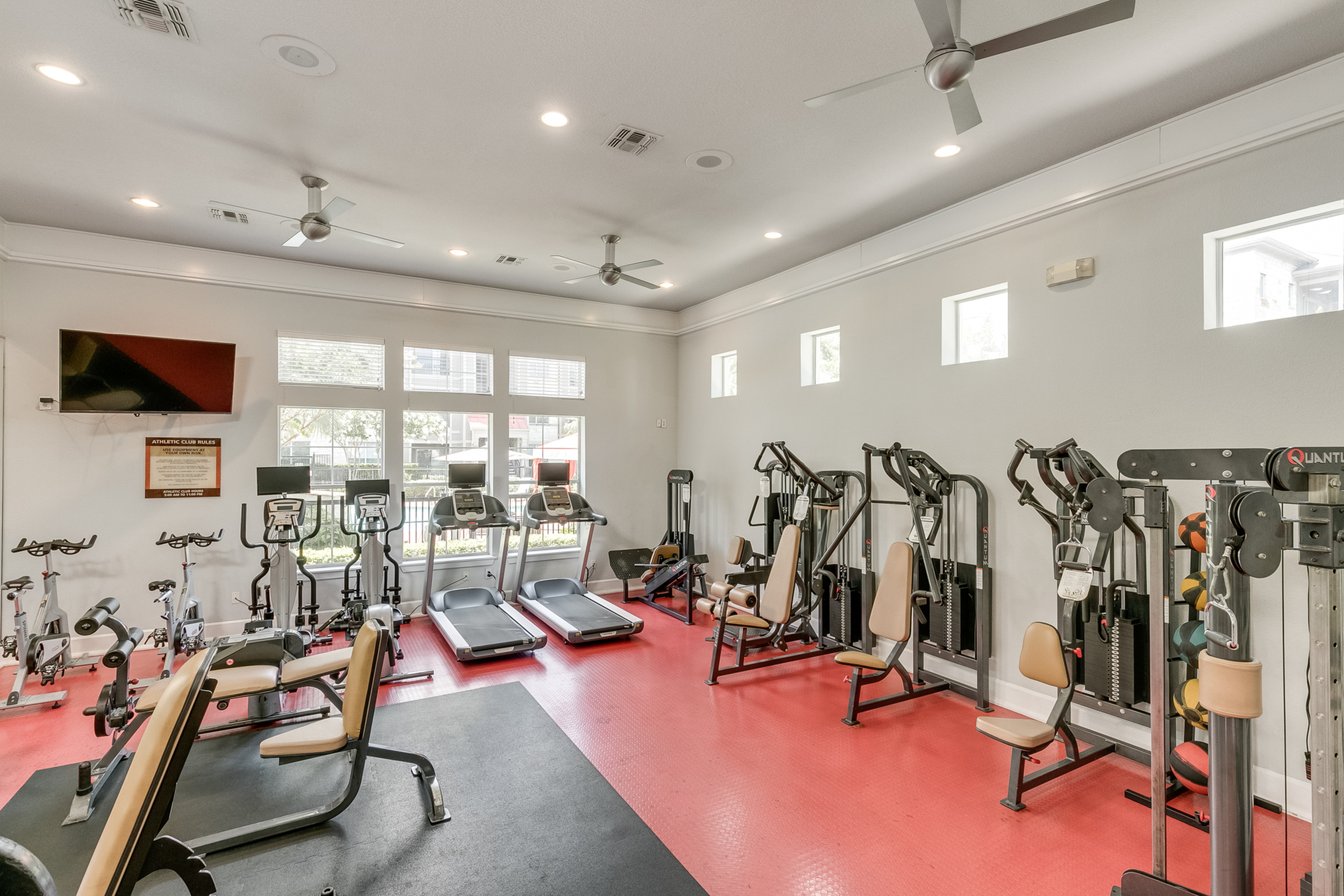 View of Fitness Center, Showing Weight Benches, Cardio Equipment, Medicine Balls, and Flat Screen TV at Retreat at Stafford Apartments
