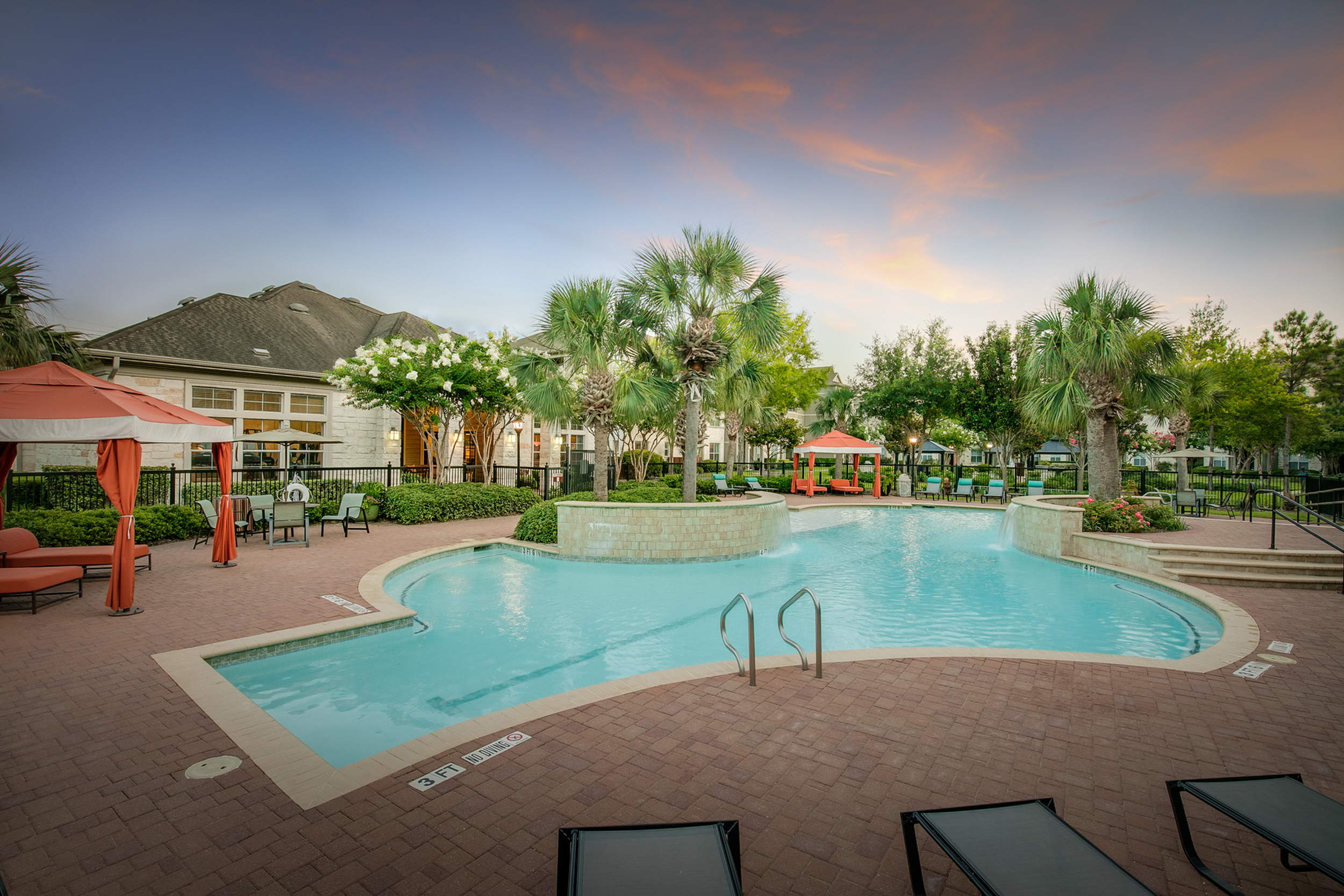 View of Resort Style Pool, Showing Cabanas, Loungers, Waterfall, and Loungers at Dusk at Retreat at Stafford Apartments