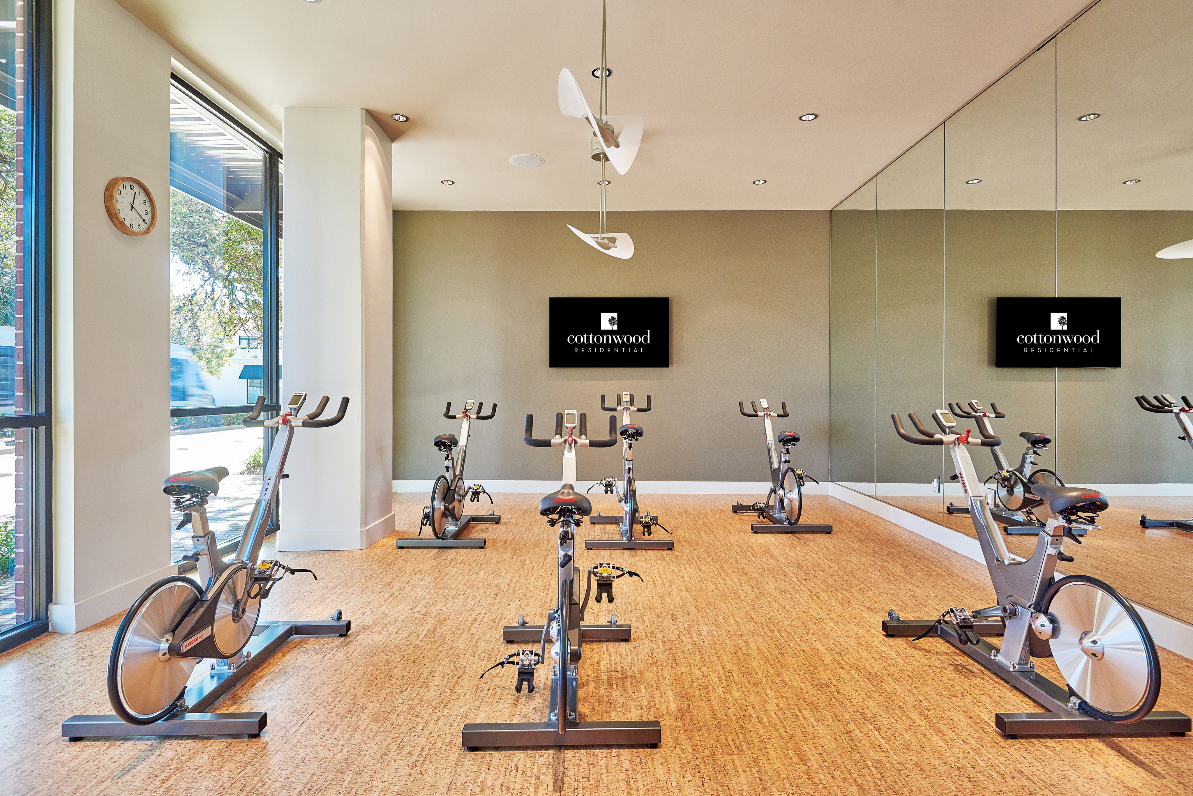 View of Spinning Room, Showing Stationary Cycles, TV, and Mirrors at 3800 Main Apartments