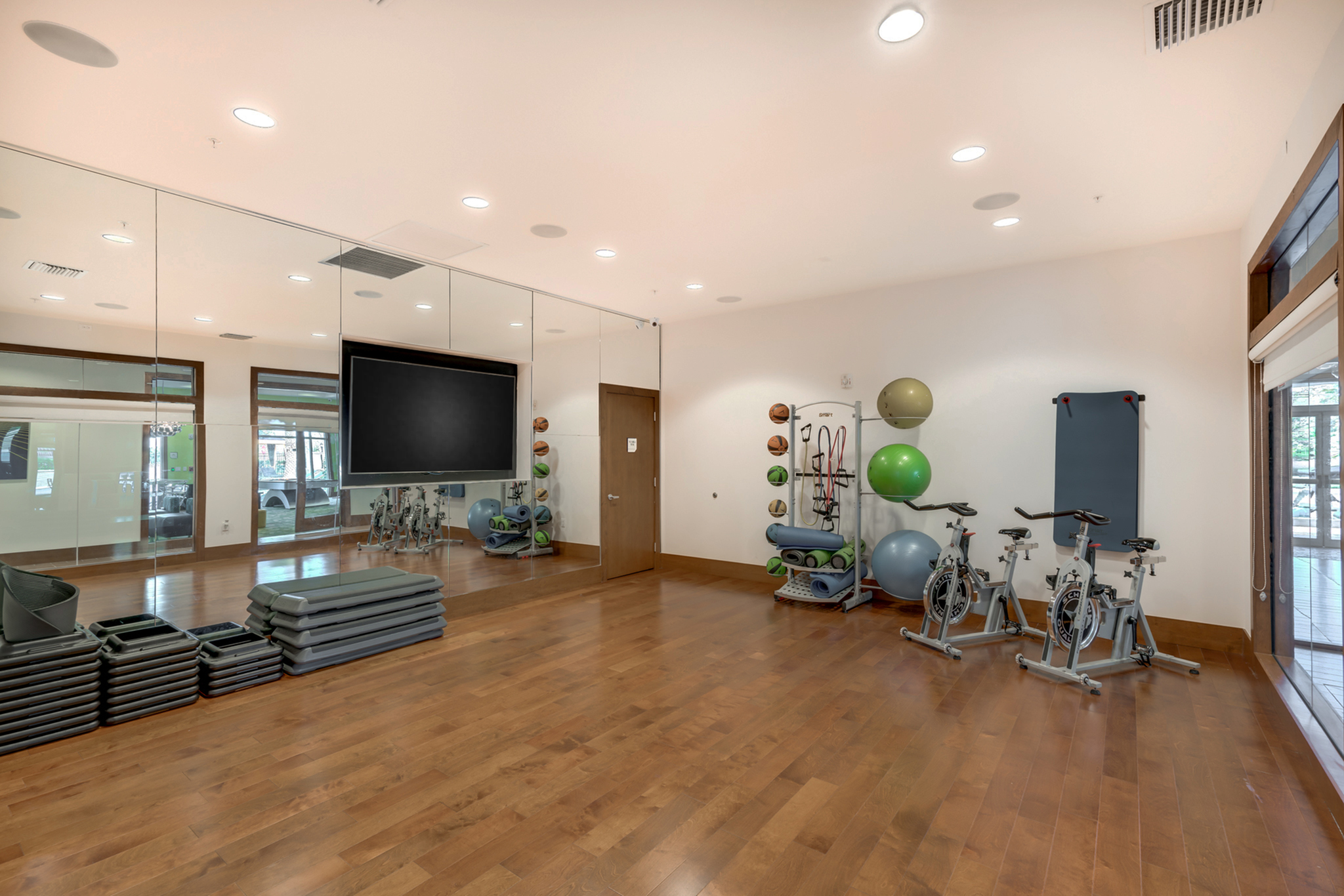 View of Yoga Space, Showing Stationary Bicycles, Exercise Balls, Medicine Balls, and Yoga Mats, TV at The Marq Highland Park Apartments