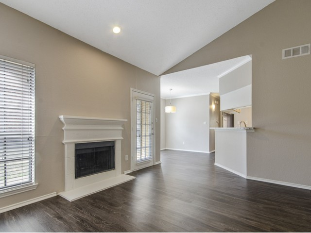 View of Renovated Apartment Interior, Showing Living Room with Fireplace, Plank Flooring, and Adjacent Dining Room at Spring Pointe Apartments