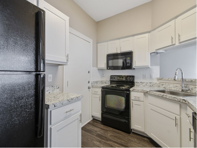 View of Renovated Apartment Interior, Showing Kitchen with Electric Appliances, Plank Flooring, and Oversized Sink at Spring Pointe Apartments