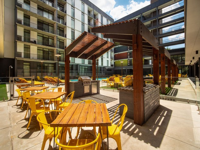 View of Pool Area, Showing Grilling Areas, Picnic Tables and Chairs, and Apartments in Background at 935M Apartments
