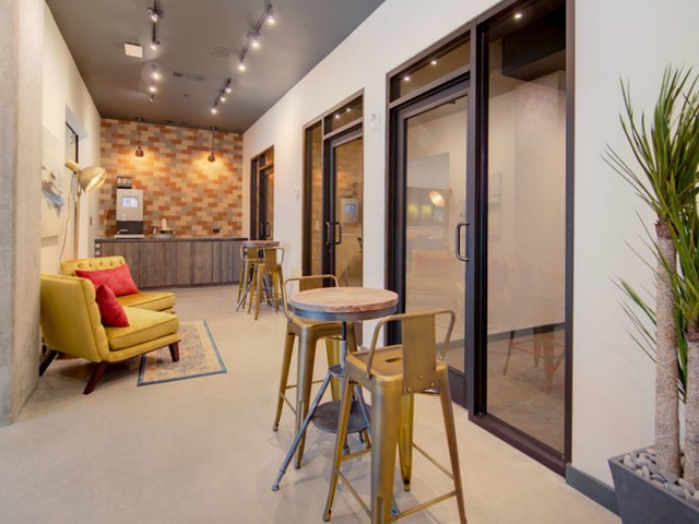 View of Coworking Spaces, Showing Private Offices, Seating Areas, and Café Bar at 935M Apartments