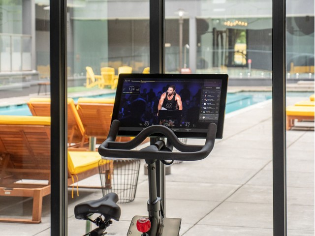 View of Fitness Center, Showing Peloton Bike with Video on Screen, and Window View at 935M Apartments