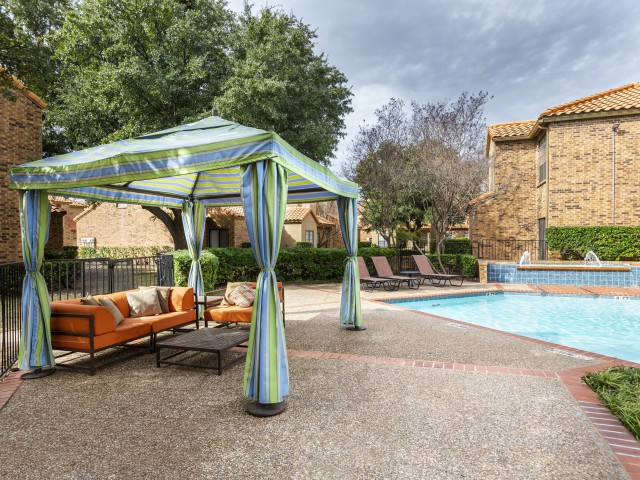 View of Resort Style Pool, Showing Outdoor Seating With Cabanas, Loungers, and Apartment Building Exterior at Spring Pointe Apartments
