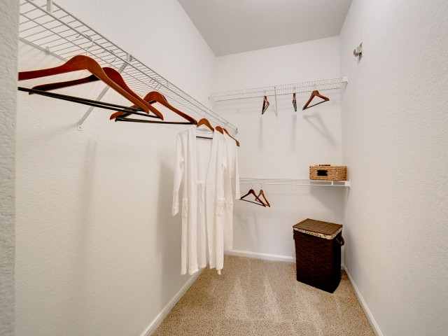 View of Classic Apartment Interior, Showing Closet with Hangers, Clothes Hanging, and Hamper at Stonebriar of Frisco Apartments