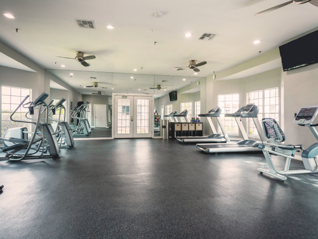 View of Fitness Center, Showing Cardio Equipment, Ceiling Fan, and Flat Screen TV at Solara Apartments