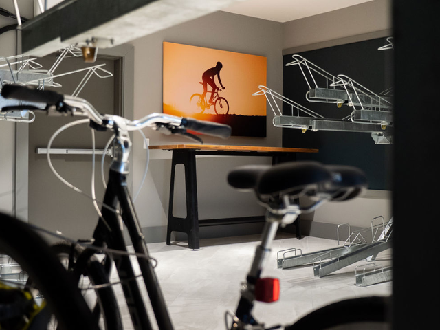 Enjoy Our Bike Workshop and Storage, With View of Hanging bike racks and workshop table at Murano at Three Oaks Apartments