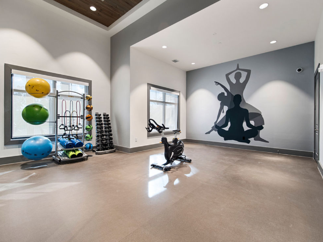 Enjoy Our Spin Room and Yoga Flow Studio, With View of Showing spin bike, open yoga space, and exercise equipment at Murano at Three Oaks Apartments