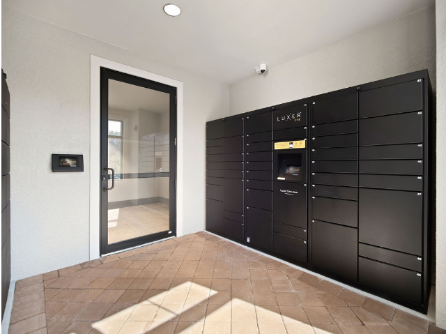 View of Package Locker and Refrigerated Grocery Storage, Showing Automated Package Lockers with Cold Grocery Delivery Storage Room at Murano at Three Oaks Apartments