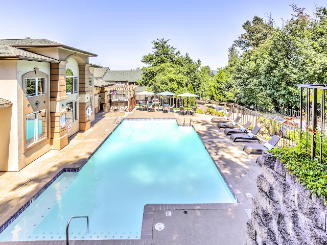 View of Swimming Pool at Scott Mountain by the Brook Apartments also showing lounge chairs, umbrella, and community clubhouse.