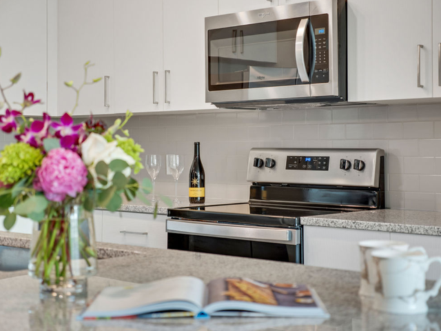 View of Flowers, Open Cookbook, and Wine Bottle on Kitchen Island with Countertops and Cabinets in the background at Murano at Three Oaks Apartments.