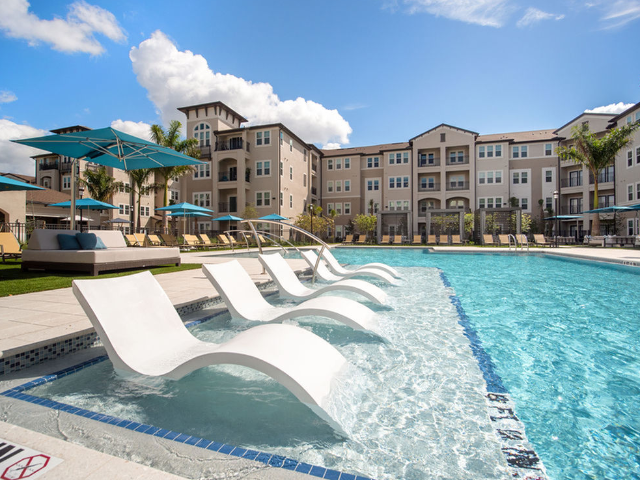 View of Courtyard Interior Area with Sun Shelf, Resort Pool, and Cabanas at Murano at Three Oaks Apartments