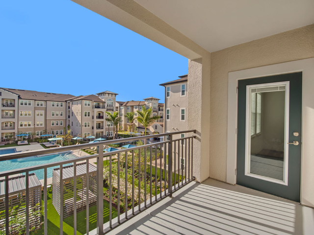 Enjoy Our Private Balconies, With View of Balcony Area and Door at Murano at Three Oaks Apartments