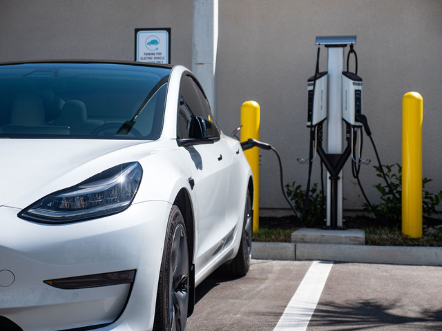 View of electric car at electric car charging station at Murano at Three Oaks Apartments