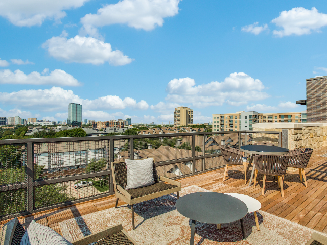 Enjoy Our Rooftop Lounge, With View of Seating Areas, City Views, and Fencing at The Hudson Apartments