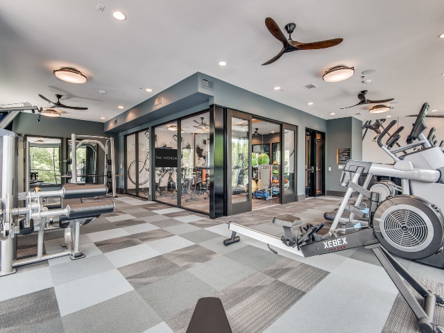 Enjoy Our Fitness Center, With View of Weight Machines, Cardio Machines, and View of Spin Studio at The Hudson Apartments