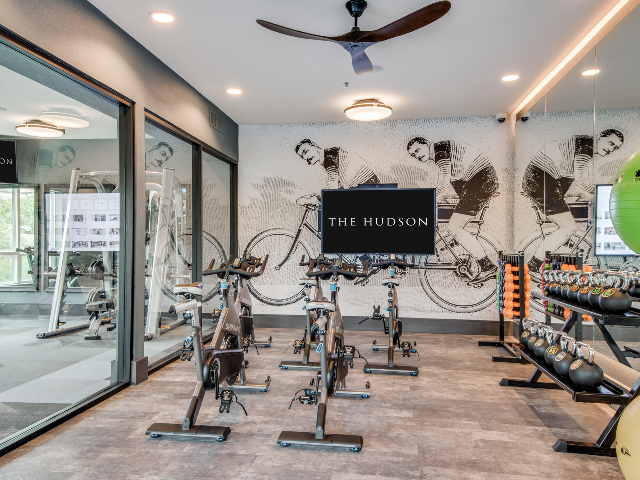 Enjoy Our Spin Studio, With View of Stationary Bicycles, TV, and Exercise Balls at The Hudson Apartments