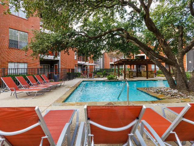 View of pool chairs and pool at 4804 Haverwood Apartments