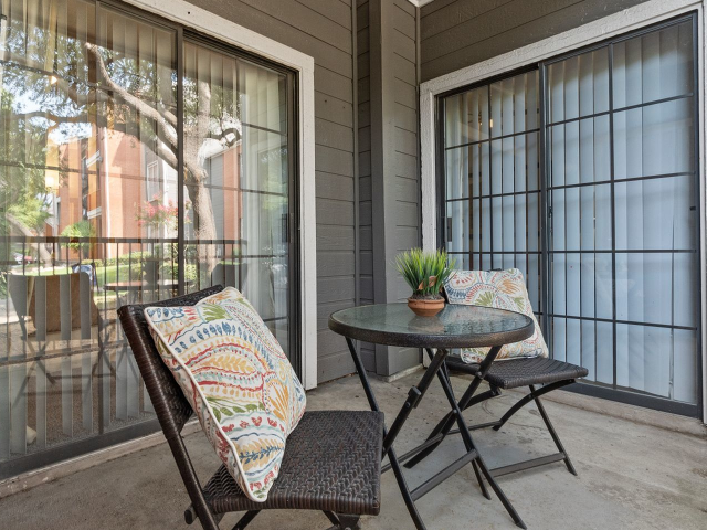 View of Patio with cafe table and chairs at 4804 Haverwood Apartments
