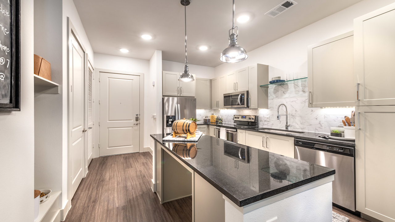 Kitchen with modern pendant lighting over the island and stainless steel appliances
