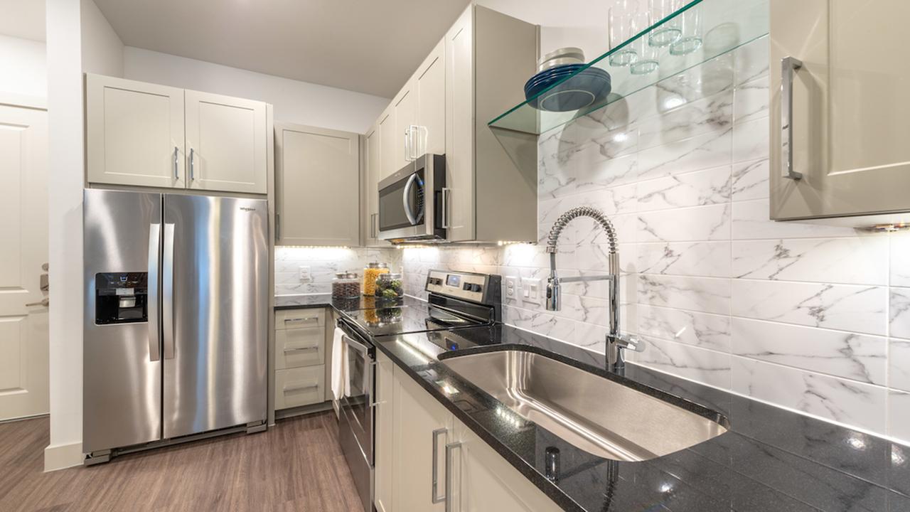 Kitchen with large farmhouse sink and tile back splash