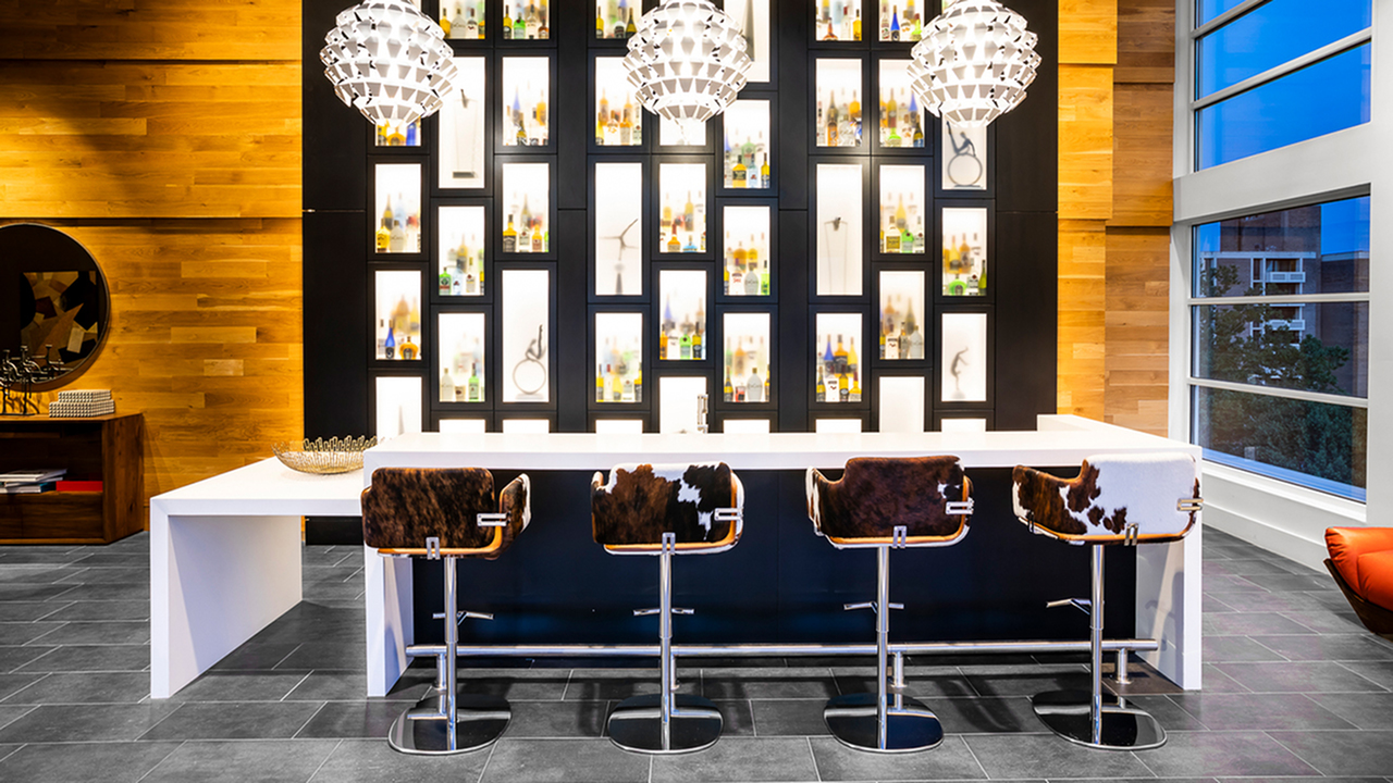 Resident lounge wet bar featuring a bar area with decorative pendant lighting
