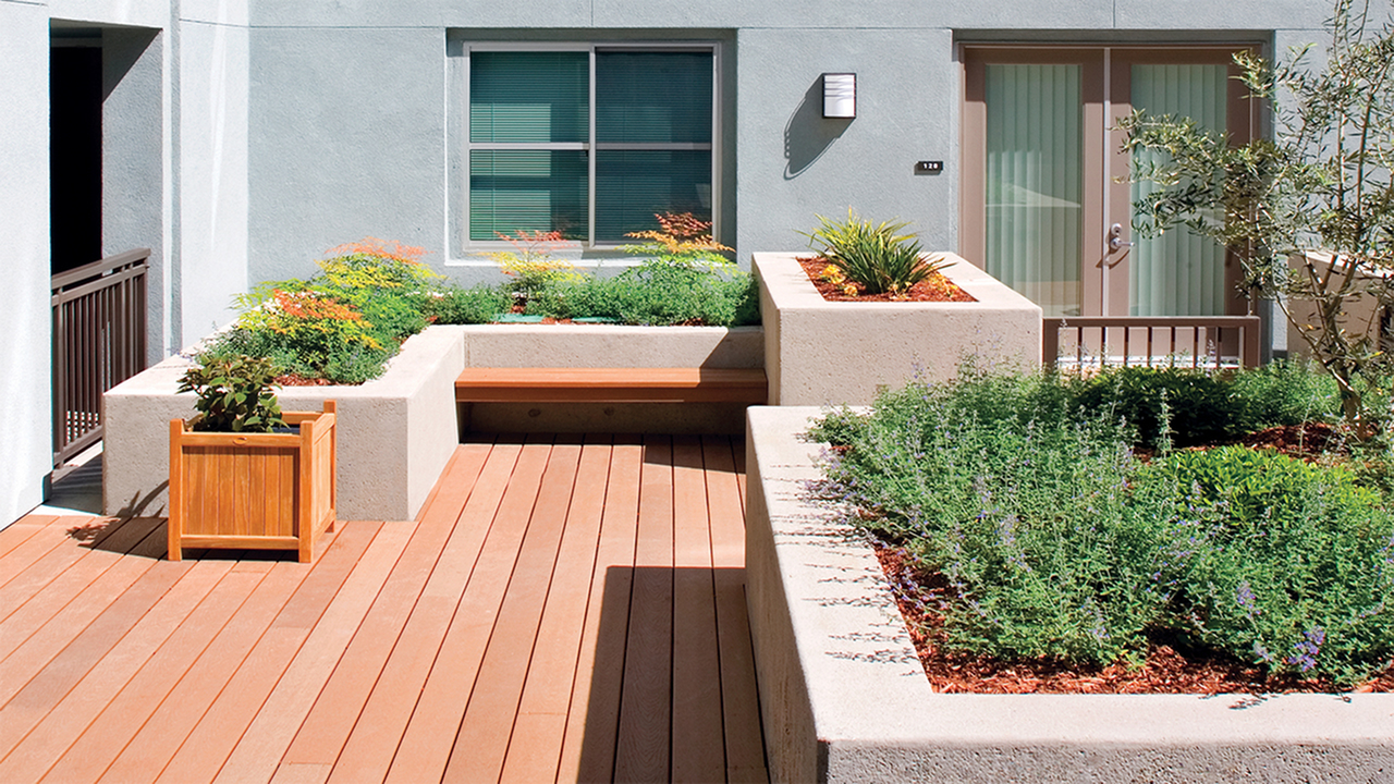 Outdoor courtyard with wood decking and raised flower beds with seating