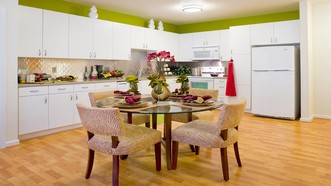 Large corner kitchen with custom white cabinetry and tile back splash