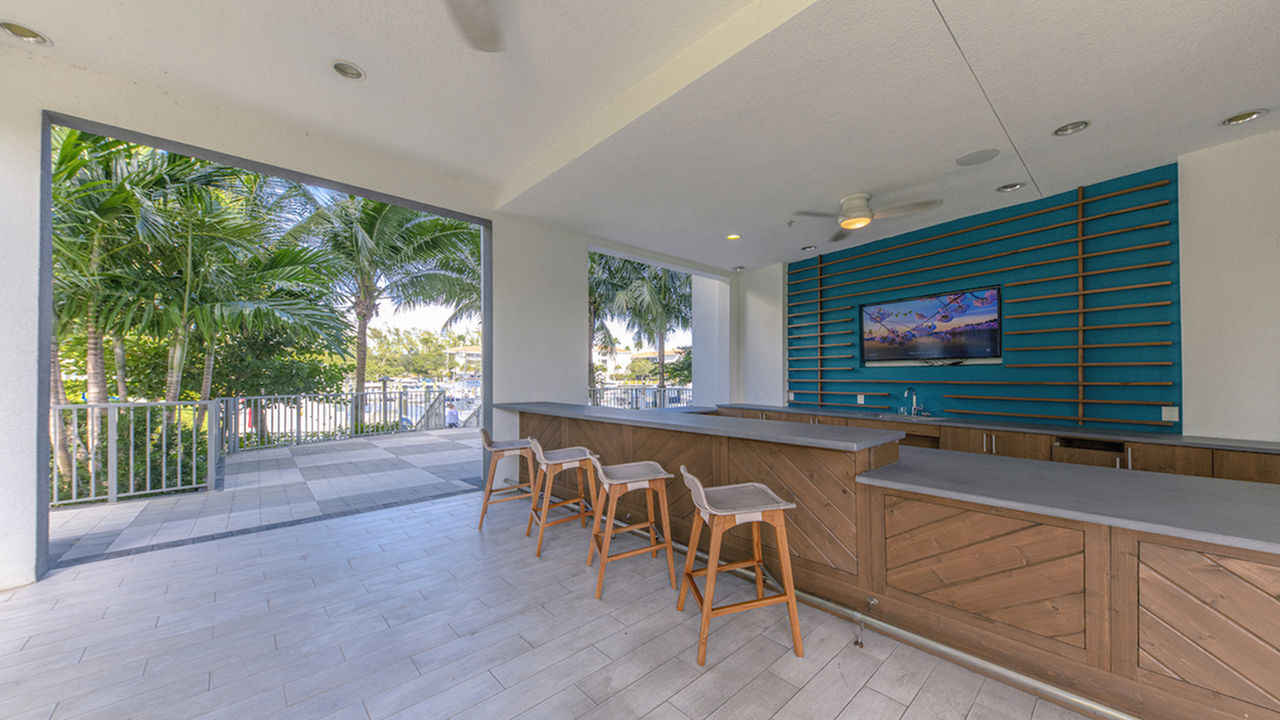 Outdoor kitchen featuring bar seating and wall mounted television