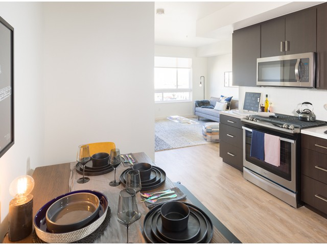 Apartment in downtown LA featuring sustainable wood flooring and stainless steel appliances