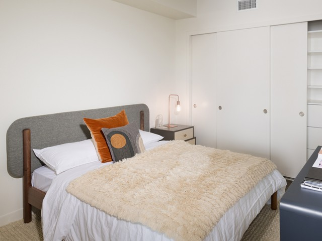 Carpeted bedrooms shown underneath a bed showing a room with custom cabinetry