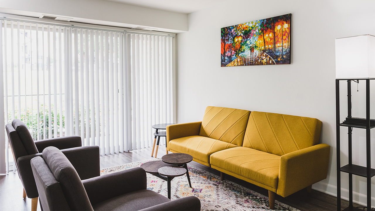 Living room with mustard sofa, two black chairs, floor lamp and tall windows