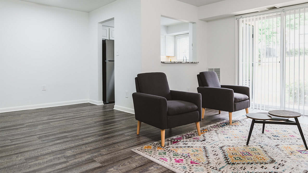 Living area with two brown chairs, patterned rug and plank wood flooring