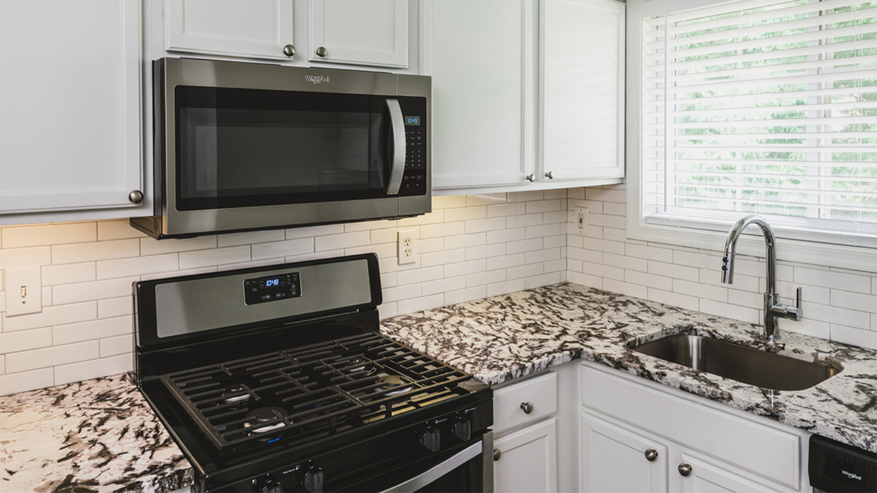 Modern upgraded kitchen with granite counter, white cabinets and stainless microwave and range