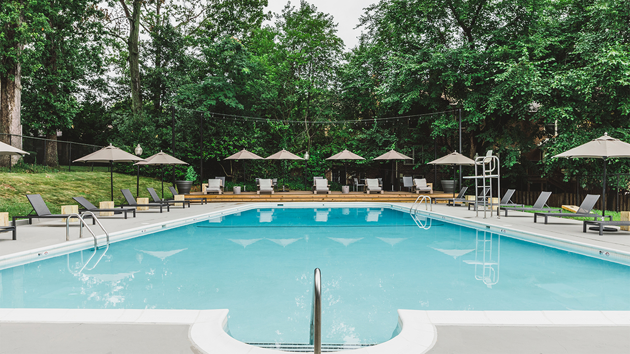 Large pool and sundeck with chaise lounges and umbrellas