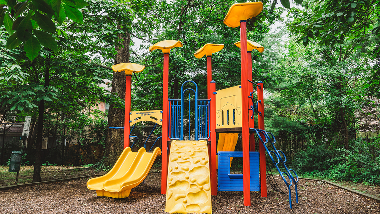 On site children\'s playscape with slides and climbing features