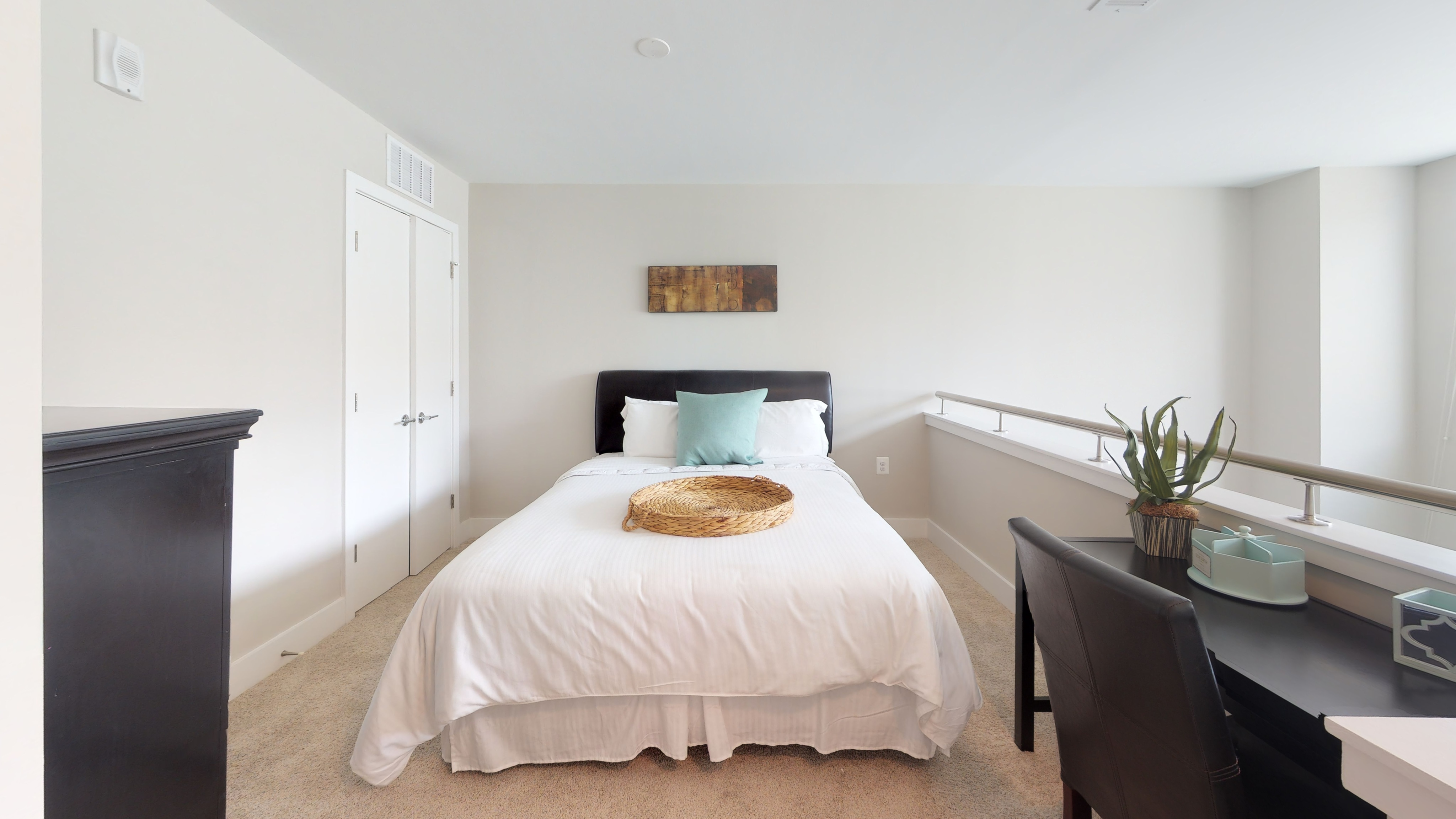 Loft bedroom with white bed and wood desk