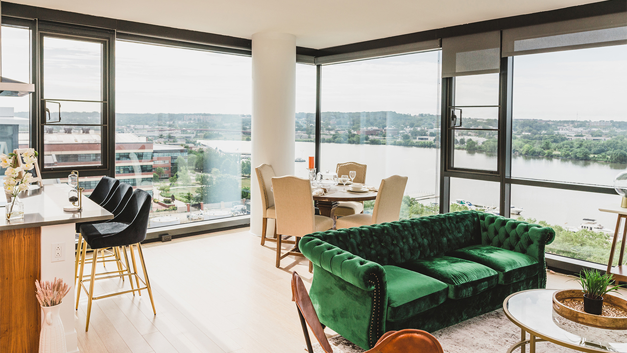Apartment interior with green velvet sofa overlooking river