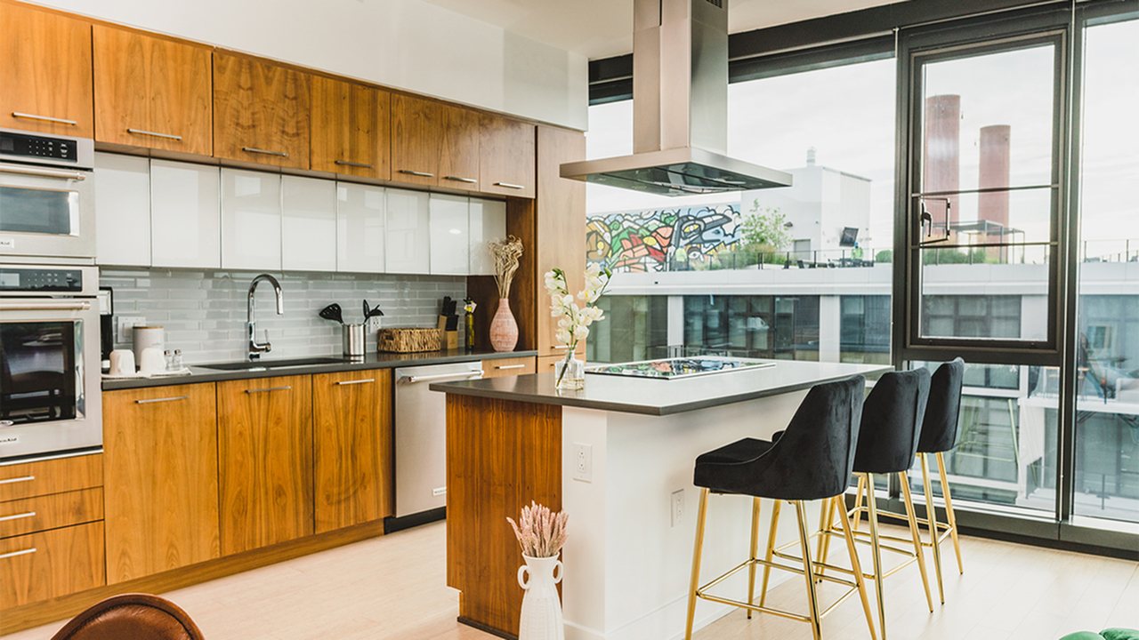 Arris kitchen with island and range hood, and three counter stools