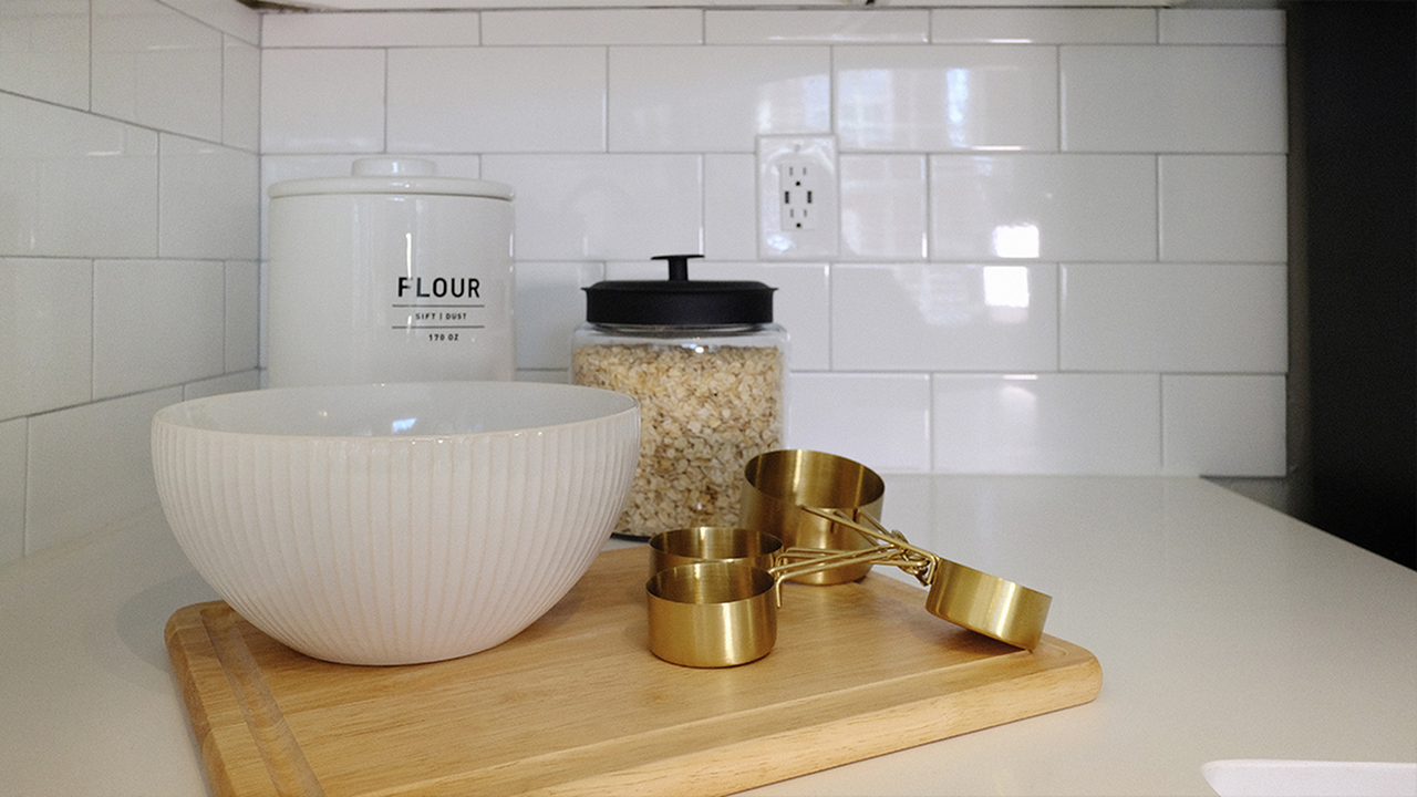 Kitchen featuring white subway tile back splash, wood cutting board, white mixing bowl, and gold measuring cups