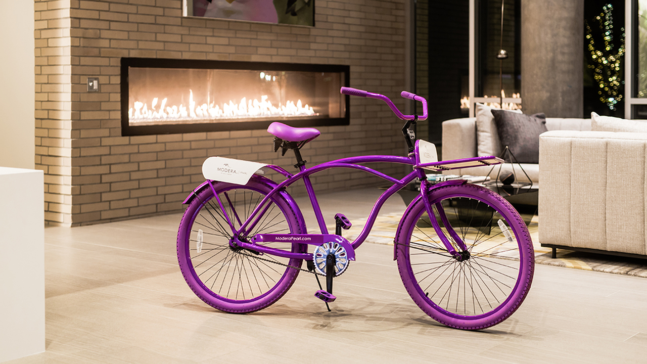 Resident lounge at night with fireplace lit and a Modera bicycle in center