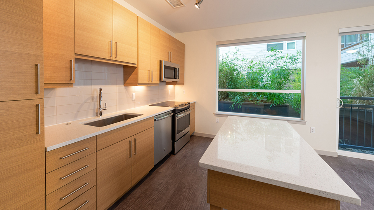 Open concept kitchen with quartz counter tops and large subway tile back splash