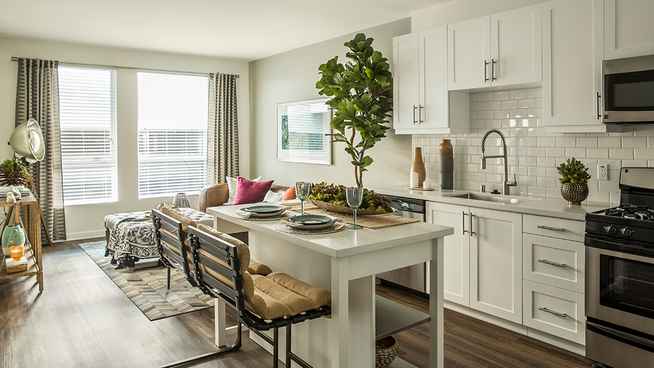 Kitchen area with island and large windows.
