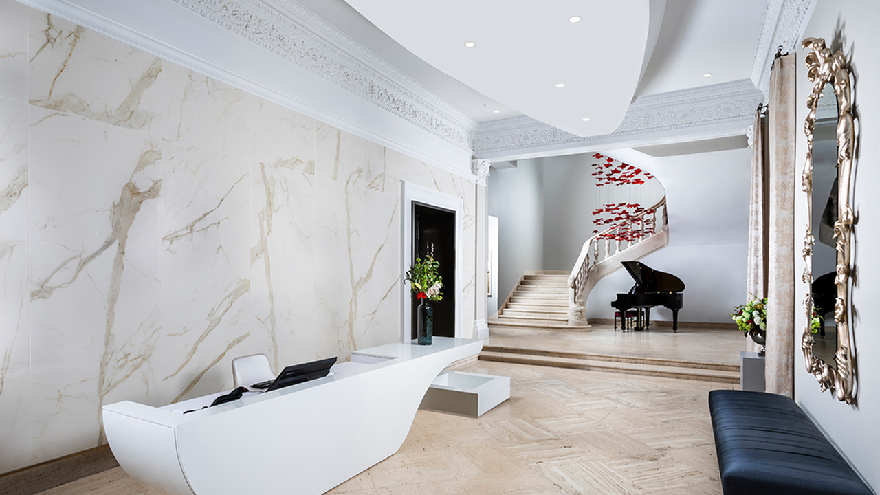 Main foyer with travertine flooring and marble wall behind concierge desk