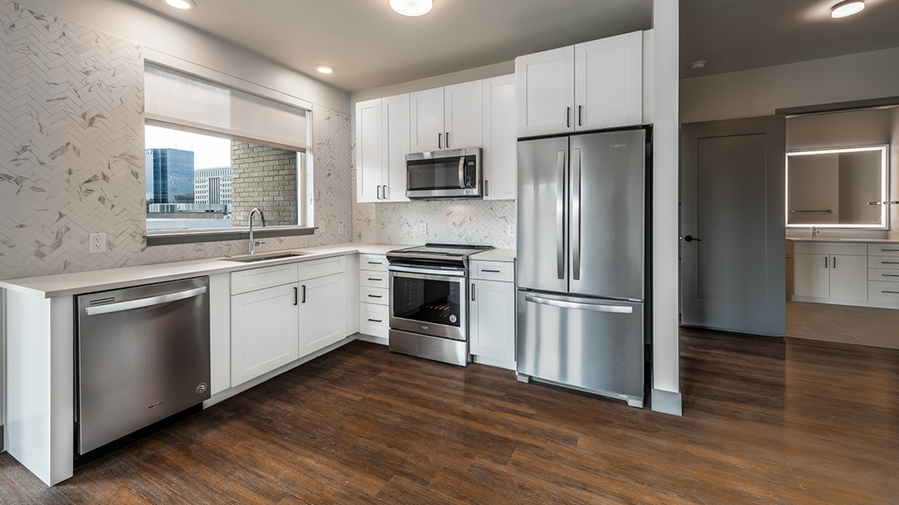 Open concept kitchens with stainless steel appliances, stunning backsplash, and plank wood-like flooring
