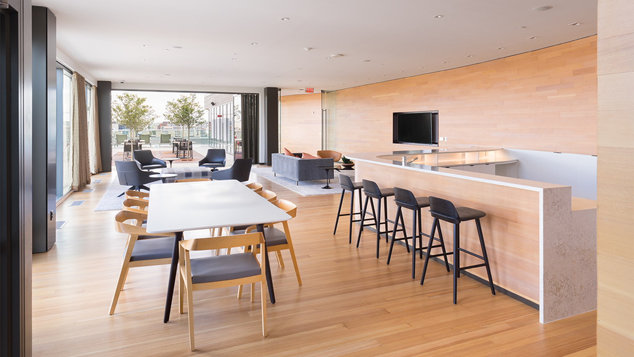 Roof clubroom featuring 80-inch TV lounge, kitchen, bar seating and communal dining table